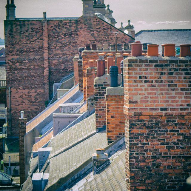 row-of-repaired-brick-chimneys